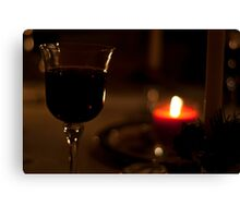 A Glass of Red wine in candle-light. Canvas Print