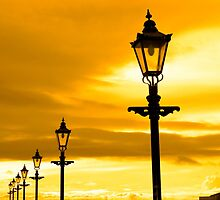 row of vintage lamps at sunset by morrbyte
