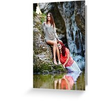 Two beautiful young women leaning on rocks beside a river Greeting Card