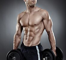 Young athletic man holding two heavy dumbbells by naturalis