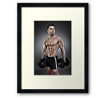 Young athletic man holding two heavy dumbbells Framed Print