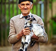 Old farmer with a baby goat by naturalis