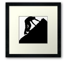 Silhouette of a man climbing a rock Framed Print