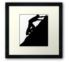 Silhouettes of a man climbing a rock Framed Print