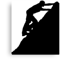 Silhouettes of a man climbing a rock Canvas Print