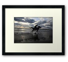 Silhouette of a man riding a horse on the beach  Framed Print