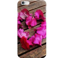 A heart from petals lying on a wooden table iPhone Case/Skin