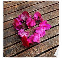 A heart from petals lying on a wooden table Poster