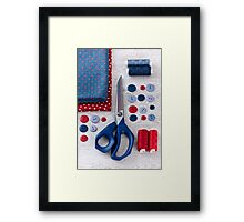 scissors, threads, fabric and buttons on wooden table Framed Print
