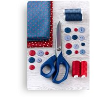 scissors, threads, fabric and buttons on wooden table Canvas Print