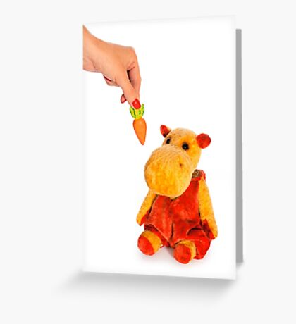 Isolated yellow hippo toy and hand with carrot Greeting Card