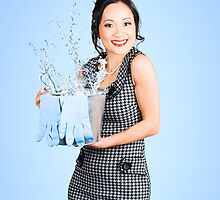 Attractive young woman holding cleaning equipment by Ryan Jorgensen