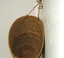 basket on a white brick wall by Clare Colins