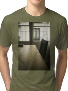 Wooden table desk and chair in empty room with window behind in beige brown colors artistic color digital photograph Tri-blend T-Shirt