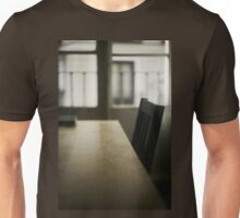 Wooden table desk and chair in empty room with window behind in beige brown colors artistic color digital photograph Unisex T-Shirt