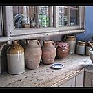 Canisters, pitchers, mortar on the sideboard by Roberta Angiolani