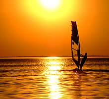 Silhouette of a windsurfer on waves of a gulf on a sunset by Sergey Sukhorukov