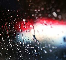 Deatil of raindrops on a car windshield at night by Reinvention