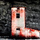 Red roadman's house with black rocks on the background by Reinvention