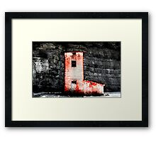 Red roadman's house with black rocks on the background Framed Print