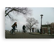 Cyclists crossing a bridge at Amsterdam Canvas Print