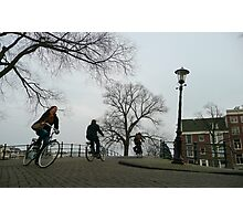 Cyclists crossing a bridge at Amsterdam Photographic Print