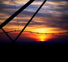 barbed wire and beams sunset by Eric Maki