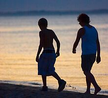 Boys walking along twilight Beach by iansimages