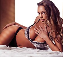 Glamour portrait of sexy young woman in lingerie lying on bed art photo print by ArtNudePhotos