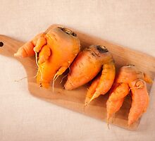 raw deformed carrot roots by Arletta Cwalina