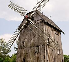 old wood windmill with sails by Arletta Cwalina