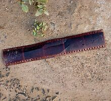 An old abandoned strip of photo film on the ground by ashishagarwal74