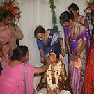 Womenfolk applying kumkum and haldi by AnIndianWedding