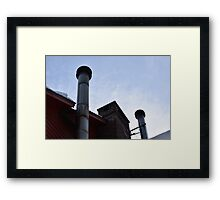 two metal smoke stacks under a blue sky Framed Print
