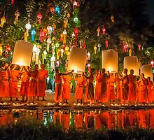 Monks releasing paper Chinese lantern at loy krathong festival of light  by Guy  Berresford