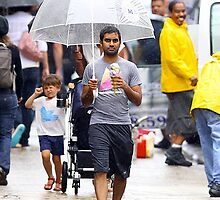 aziz ansari walking in rain with umbrella  by michaelcera