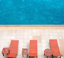 poolside deckchairs alongside blue swimming pool from top view by juat