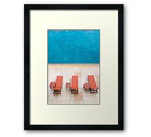 poolside deckchairs alongside blue swimming pool from top view Framed Print