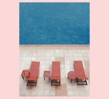 poolside deckchairs alongside blue swimming pool from top view Kids Clothes