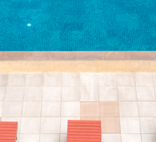poolside deckchairs alongside blue swimming pool from top view Sticker
