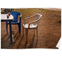 Coffee cups along with chairs and tables in a quiet location Poster