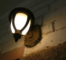 An old style electric lamp on a wall amidst dust and cobwebs by ashishagarwal74