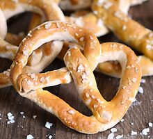 Pile of Salty Baked Bavarian Pretzels on Dark Wood by HotHibiscus