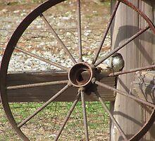 A Bird Sitting on a Old Wagon Wheel by roadsidestills