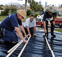 Firefighters patch roof by Larry  Grayam