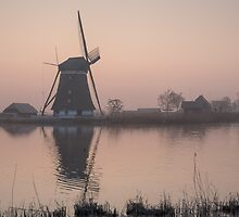 Sunrise over a cold and misty windmill by arjenroos