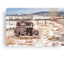 Rusty Antique Vehicle in a Field Covered with Snow Canvas Print