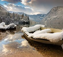 Snow covered boat on Lake Bohinj in Winter by Ian Middleton