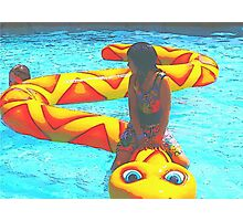 A girl sits on a snake and what could possible happen except she falls off and gets wet.. Photographic Print