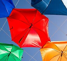 Colourful umbrellas strung up together on a blue sky background  by PhotoStock-Isra